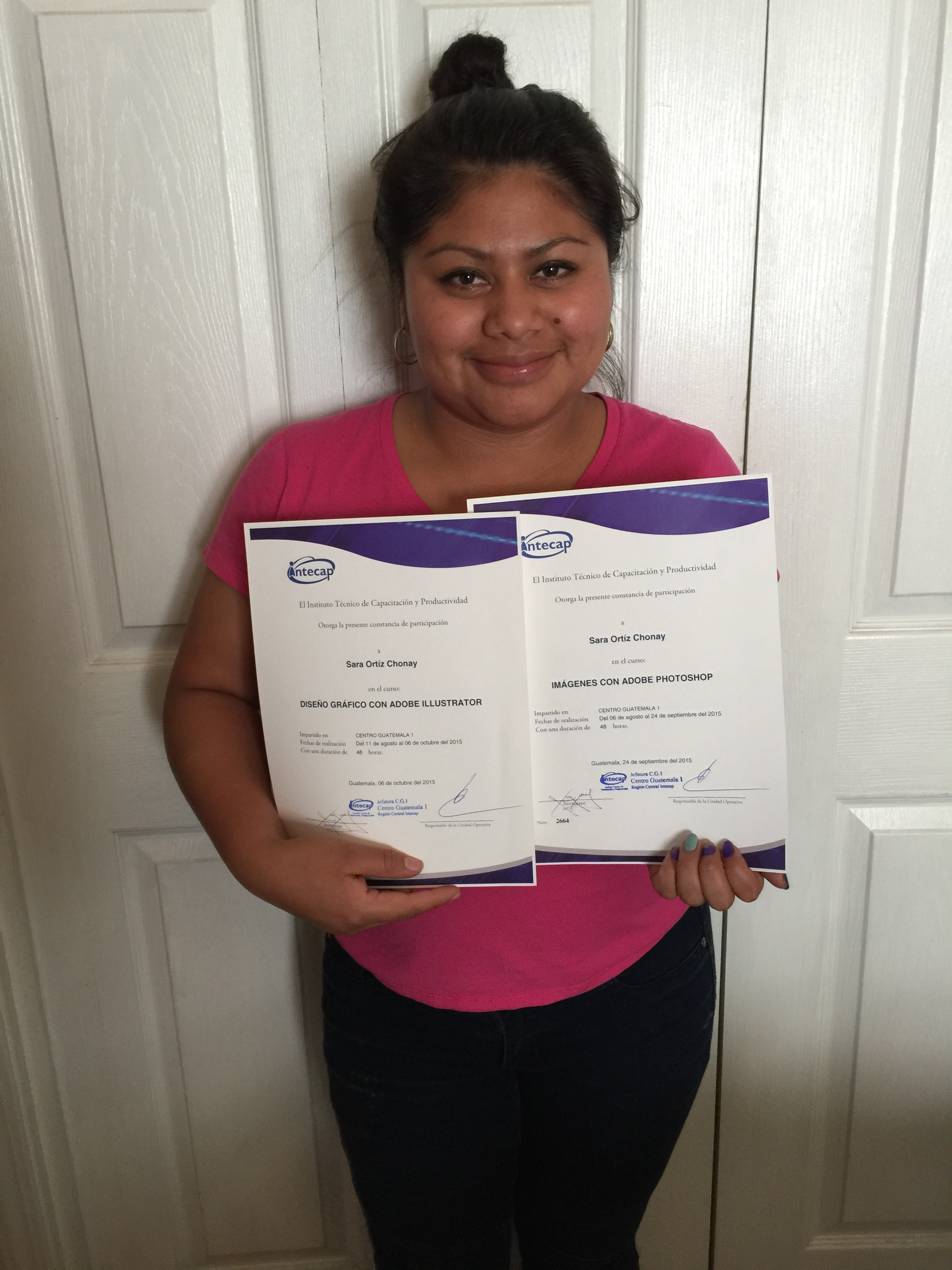 Sarah with her two diplomas in computer and phot shop