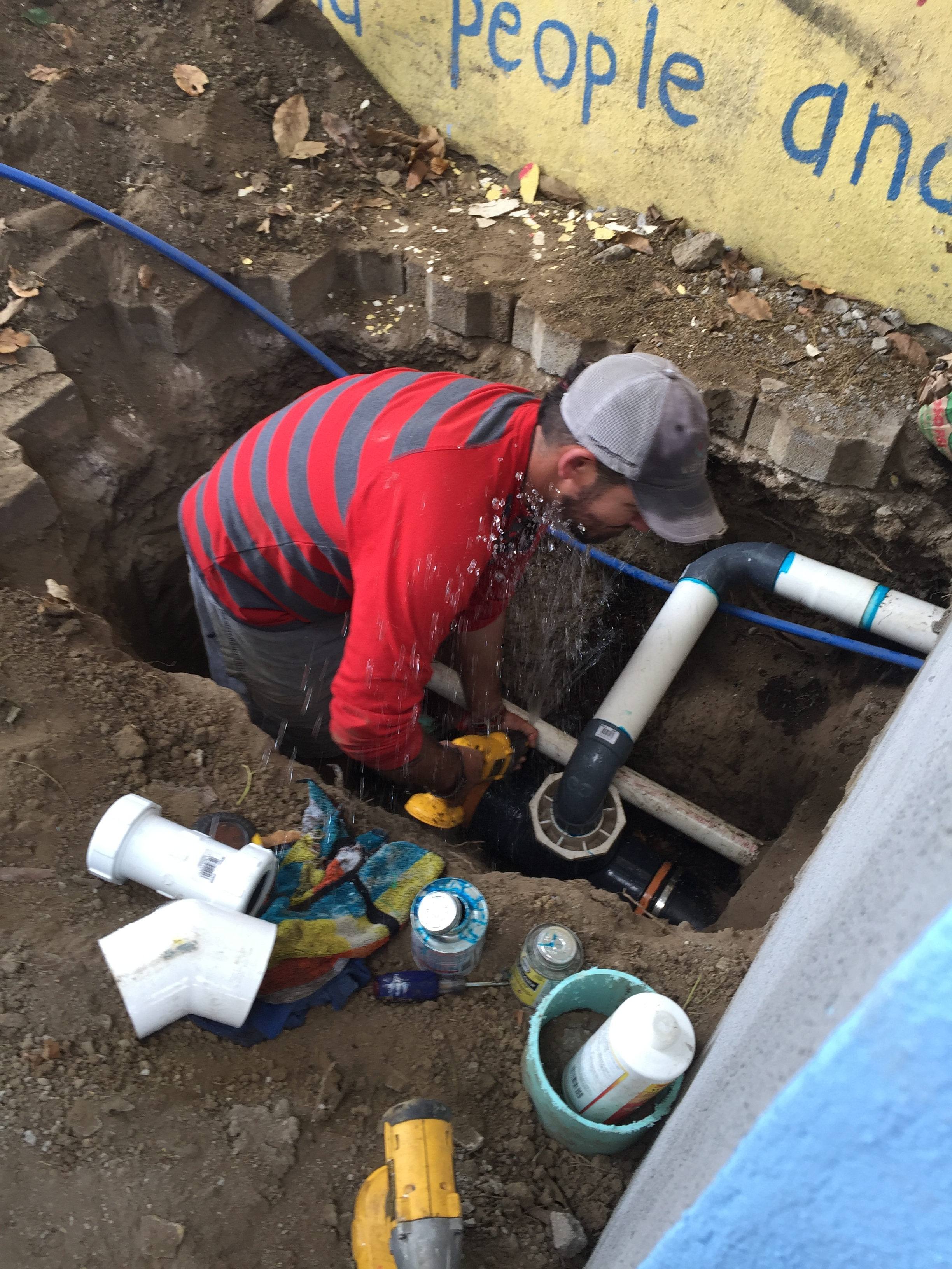 Tyson connecting the sewer and water lines for the new restrooms